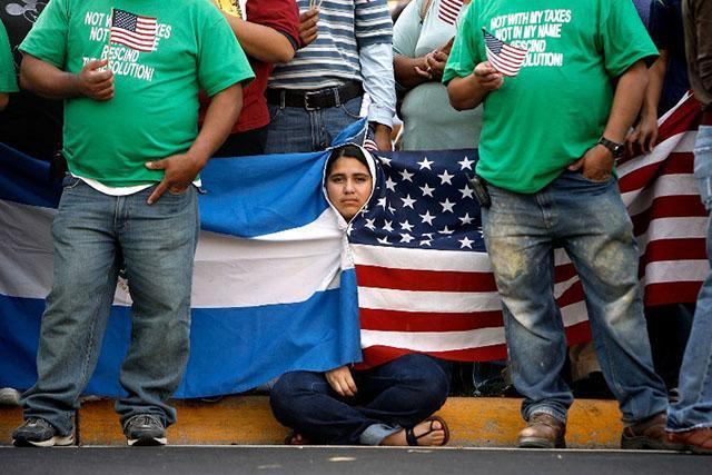 Una joven salvadoreña se arropa con las banderas de Estados Unidos y El Salvador durante una manifestación de 2007 en Manassas, Virginia,contra medidas para frenar la migración. Foto AFP/Chip Somodevilla