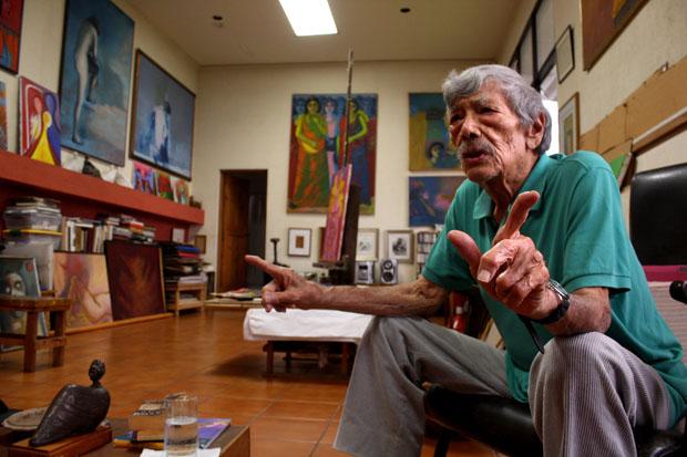 El pintor Carlos Cañas rodeado de gran parte de su obra en su estudio en la Colonia Escalón de San Salvador.
