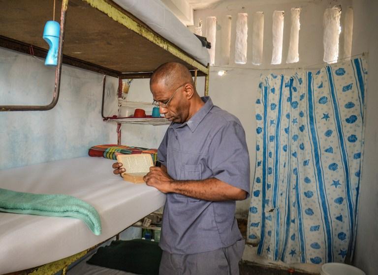 Así luce una celda en esta cárcel de alta seguridad de Cuba, en la que cada interno duerme sobre su catre. En la imagen, un reo lee un libro durante la visita. Foto Adalberto Roque (AFP).