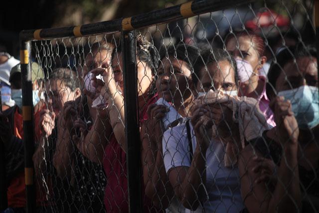 Familiares de reos de la penitenciería de Comayagua esperan noticias sobres sus familiares en la cerca perimetral de la cárcel.