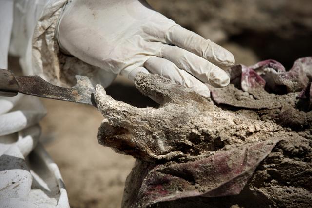Israel Ticas en el proceso de pulir un cadáver, utilizando un instrumento que le sirve para desmoronar la tierra de los cuerpos.