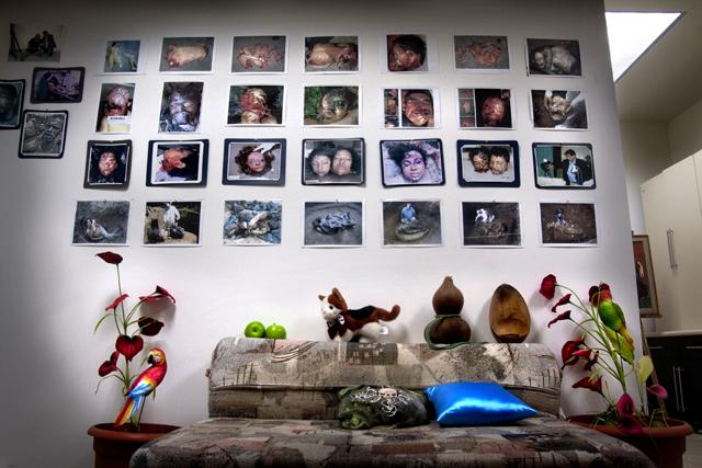 Parte de la oficina del criminalista: bajo un mural con fotos de cadáveres mutilados se encuentra un sofá-cama en el que suele dormir. Sobre el mueble descansa su colección de peluches y almohaditas.