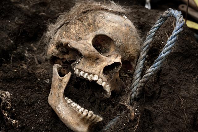 El cráneo de una chica asoma de la tierra. Aún lleva el lazo con el que fue asfixiada.