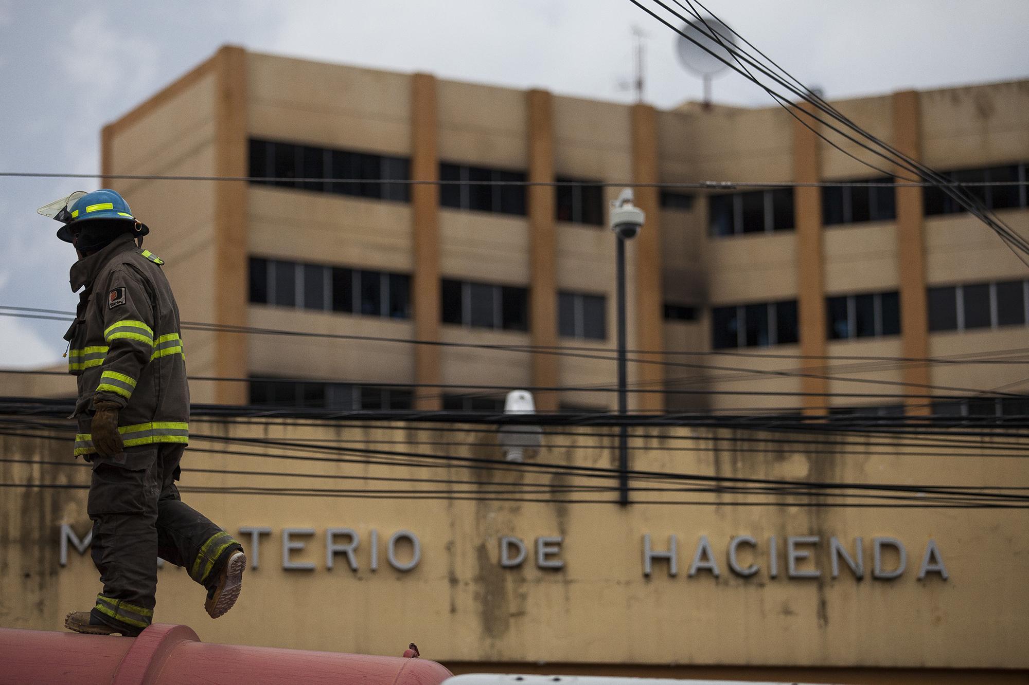 Un miembro del Cuerpo de Bomberos trabaja en medio de la evacuación de los empleados del Ministerio de Hacienda, donde un incendio consumió el cuarto nivel del ala C de la torre número tres. Las autoridades reportaron una persona fallecida y 18 lesionados (ocho de gravedad) Foto: Víctor Peña