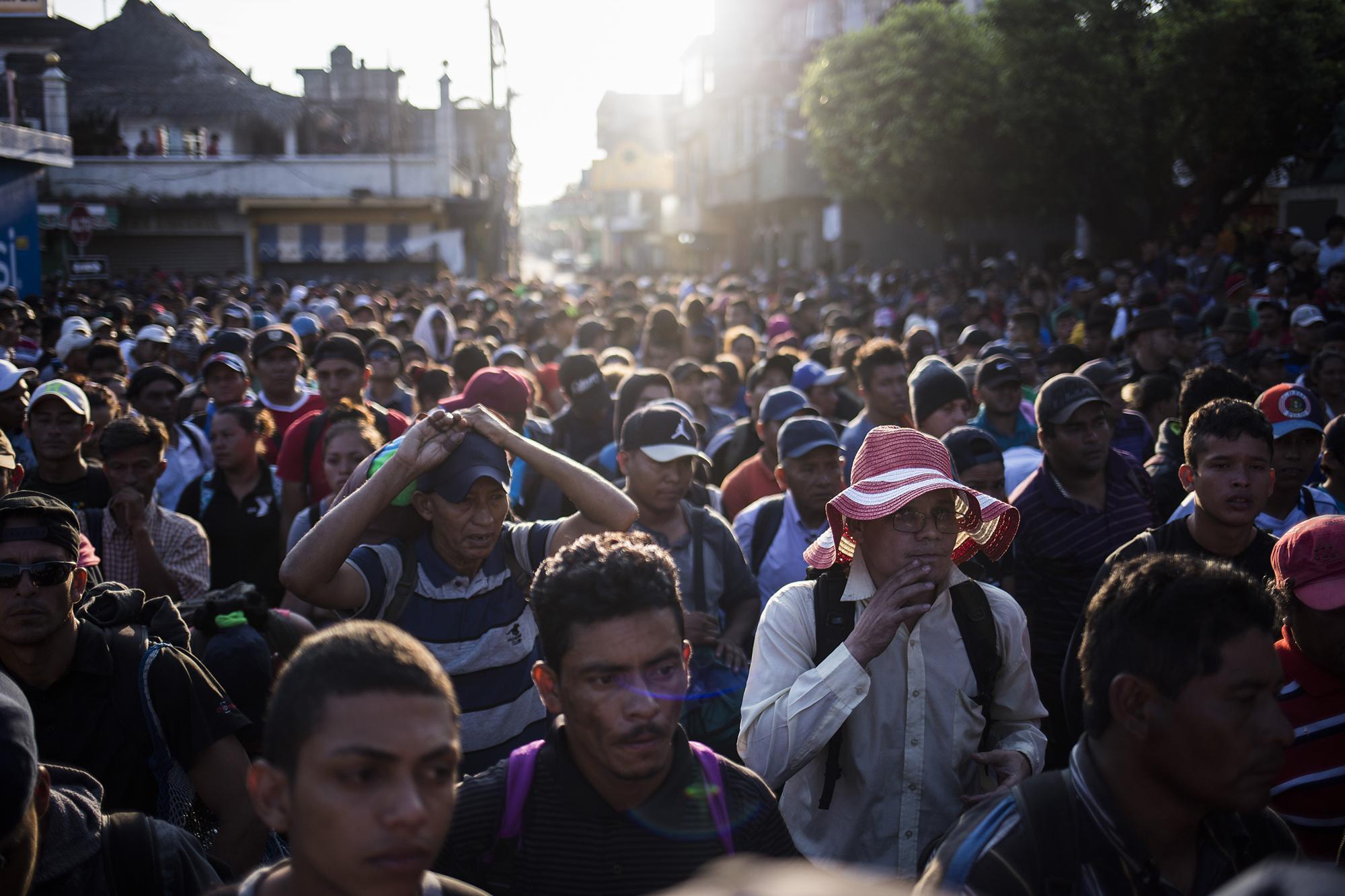 Una caravana de migrantes espera frente al portón de la aduana guatemalteca, en el paso de la frontera Tecún Umán. Más de 2 mil personas, procedentes de los países del Triángulo Norte de Centroamérica, llegaron a este lugar para cruzar a México y caminar hacia Estados Unidos. Foto: Víctor Peña.