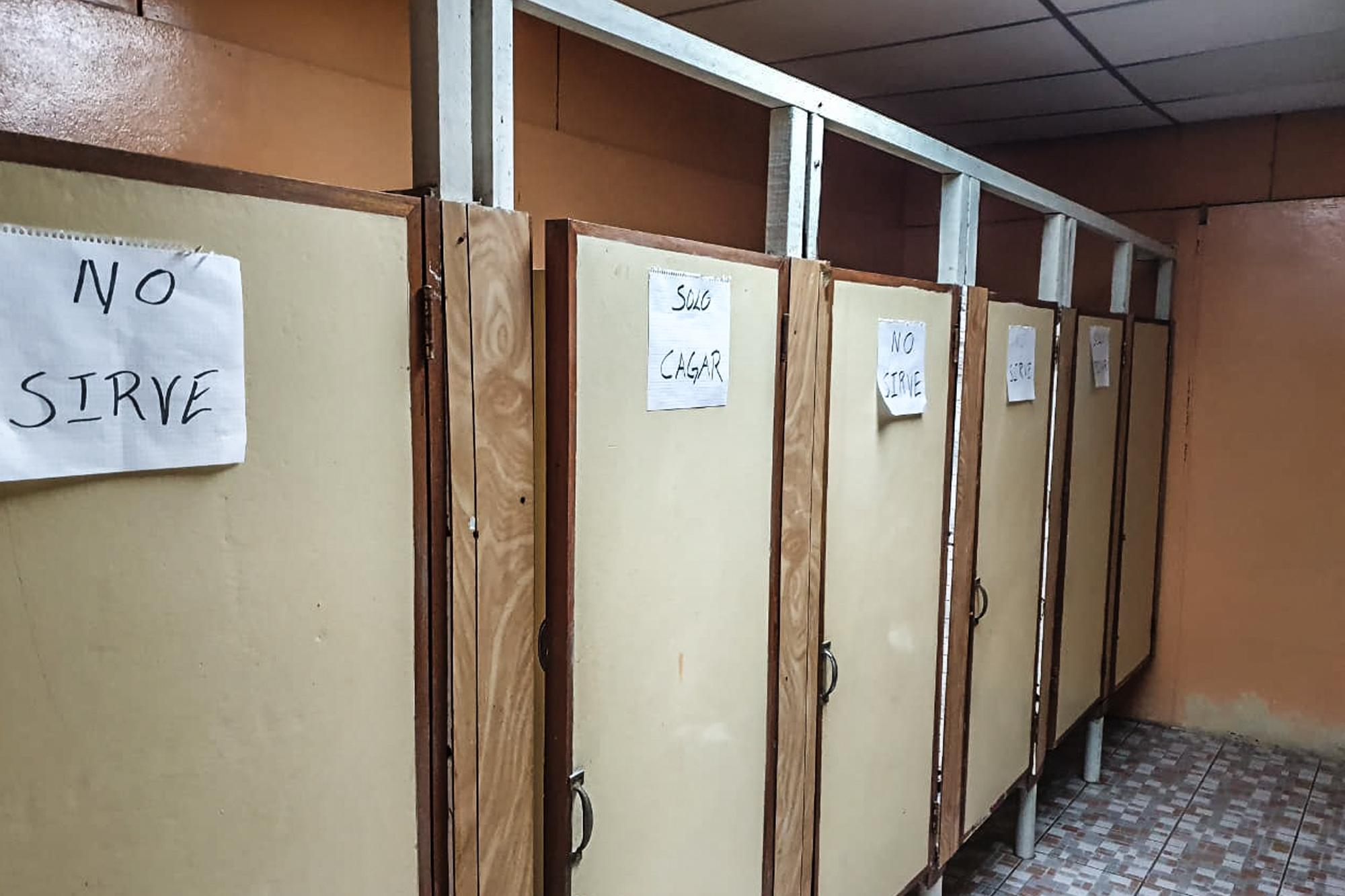 "Signs read: ""Out of order;"" and ""Shit Only."" The restroom in Villa Olímpica, a site lacking the appropriate amenities to shelter people. This facility continues to house detained Salvadorans accused of violating domestic quarantine. Image courtesy of the family."